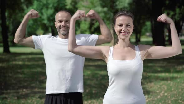 Thumbnail for Positive Man and Woman in Sportswear Showing Strength Gesture and Smiling at Camera. Beautiful