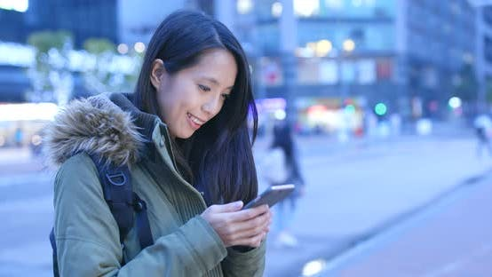 Thumbnail for Woman using mobile phone in the city at night