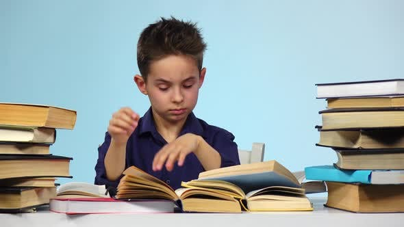 Tired Boy Sitting at a Table for a Book Falls Asleep and Wakes Up. Blue Background