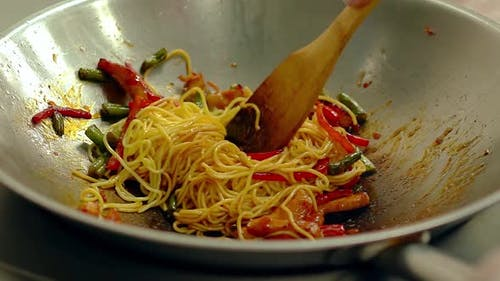 CU, Slow Motion: Cook Prepares Noodles Pasta in Frying Pan, in Oil, with Fresh Vegetables