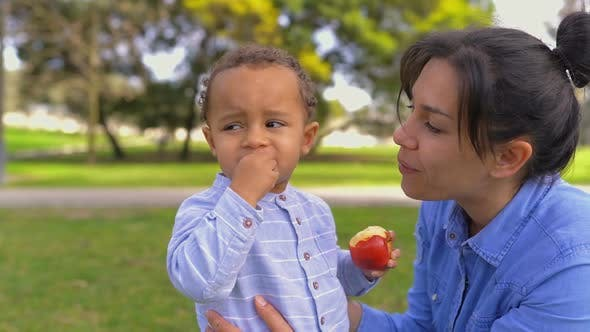 Thumbnail for Mixed-race Pretty Mother Looking at Son Eating Apple