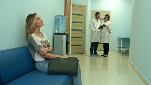 Thumbnail for Female Patient Waiting in Hospital Hall While Two Doctors Consulting