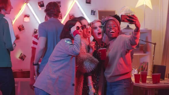 Thumbnail for Young Trendy Women Taking Selfie at Home Party and Laughing