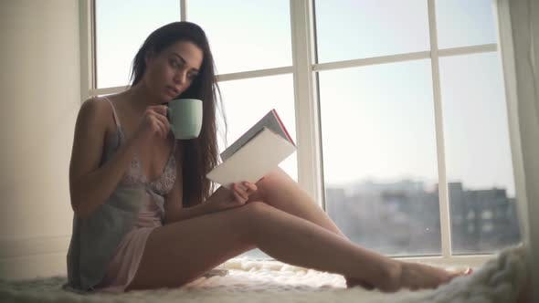 Thumbnail for Beautiful Girl in Nightie Sitting By the Wide Window. Young Woman in Pajamas Drinking Morning Coffee