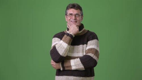 Mature Handsome Man Wearing Turtleneck Sweater Against Green Background