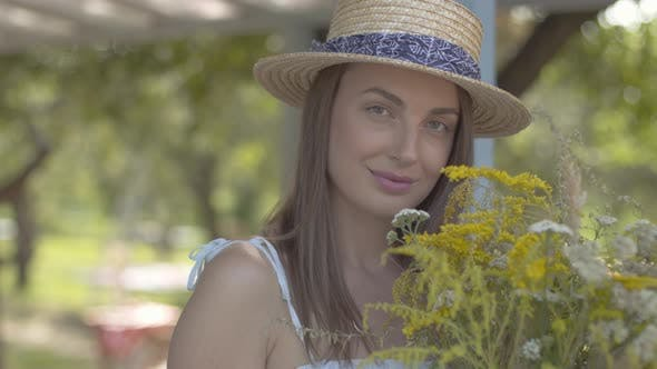 Thumbnail for Portrait Adorable Young Woman in Straw Hat and White Dress Looking at the Camera Smiling