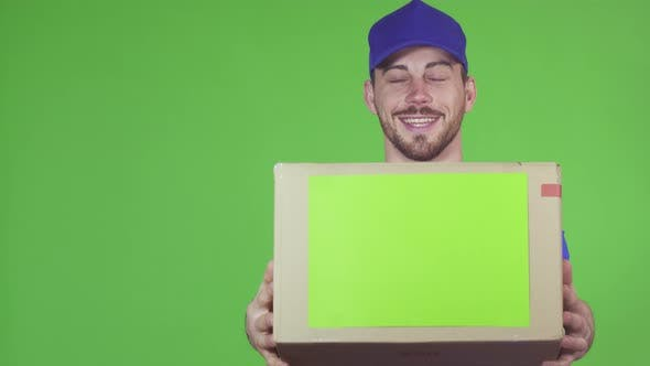 Thumbnail for Handsome Professional Deliveryman Holding Out Package To the Camera