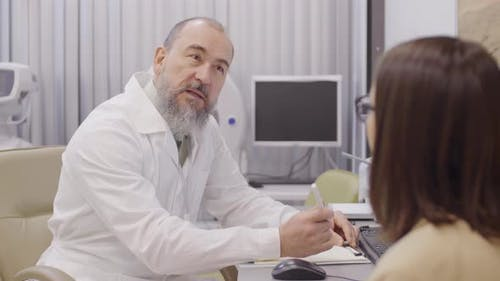Senior Ophthalmologist Talking with Female Patient