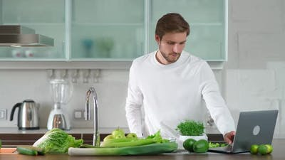 Healthy Food Man Prepares a Salad in the Kitchen Cuts Herbs and Green Vegetables to Make a Healthy