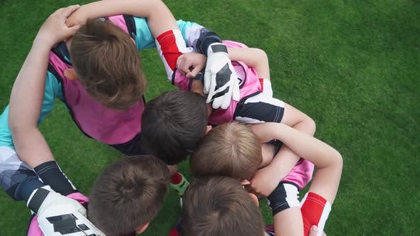 Group of Young Football Players on the Football Field, the Youth Team Stand in an Embrace, Confers