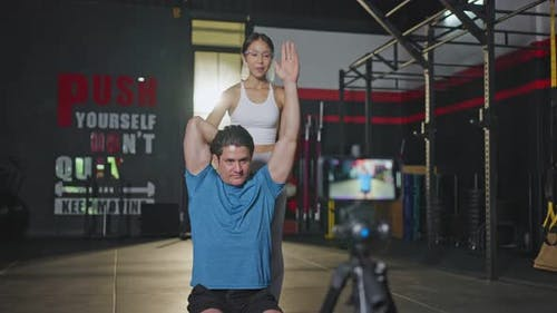 Asian yoga woman teacher wearing face shield teaching live online to Caucasian man in gym.