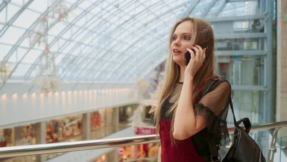 Thumbnail for Beautiful Girl Talking on Smartphone and Sitting with Shopping Bags in Mall