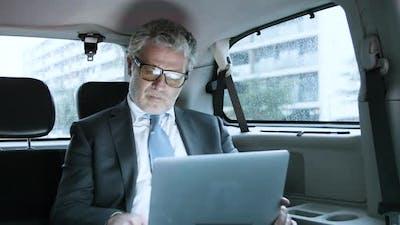 Focused Senior Businessman Using Laptop in Car