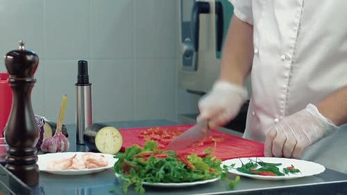 The Cook Cuts a Tomato for a Salad.