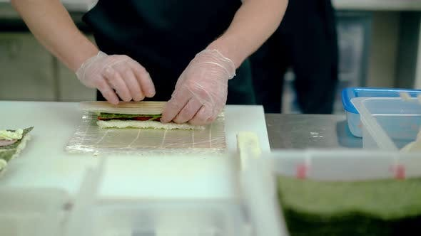 Cook Prepares Japanese Rolls with Bulgarian Pepper Cucumber Wraps with a Mat in Boiled Rice and