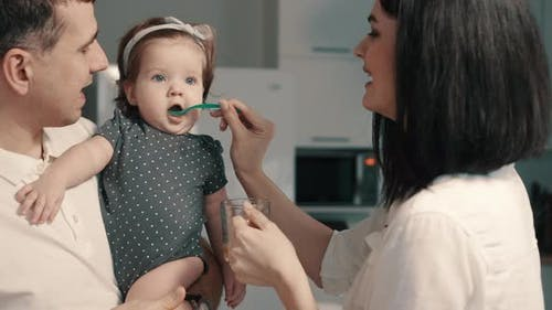 Young Parents Feed Baby Daughter at Home