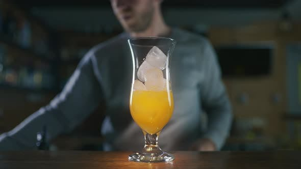 Thumbnail for Barman Adds Ice To the Cocktail and Fills Glass with Mixed Alcohol in Slow Motion, Making Cocktails