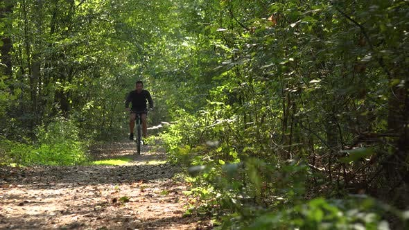 Thumbnail for A Cyclist Rides Down a Path Through a Forest - Front View