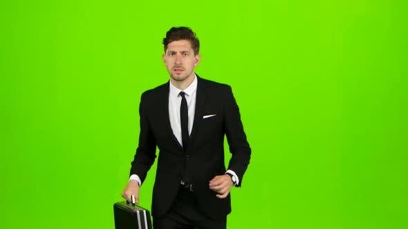 Cover Image for Man Holds a Briefcase in His Hand, He Rushes Over It. Green Screen