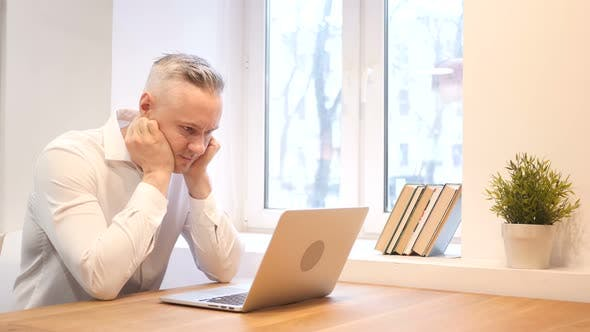Thumbnail for Middle Age Man Upset by Loss while Working on Laptop