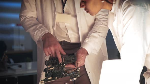 Thumbnail for Close Up of Engineer's Team Work on Motherboard Improvement in Lab