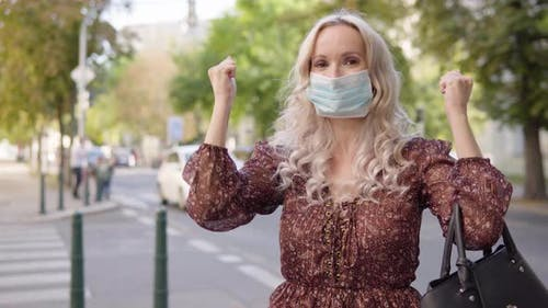 A Middleaged Caucasian Woman in a Face Mask Celebrates in an Urban Area  a Busy Road
