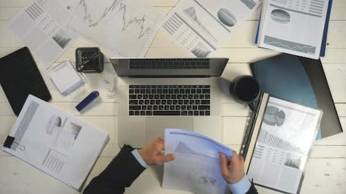 Top View Hands of Young Businessman Looking at Diagrams with Statistic on Paper and Typing Text on
