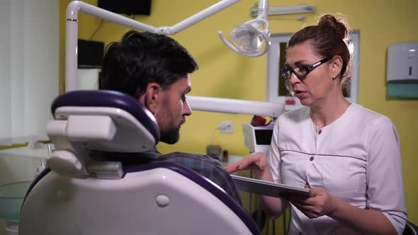 Doctor Using Tablet While Explaining X-ray Results