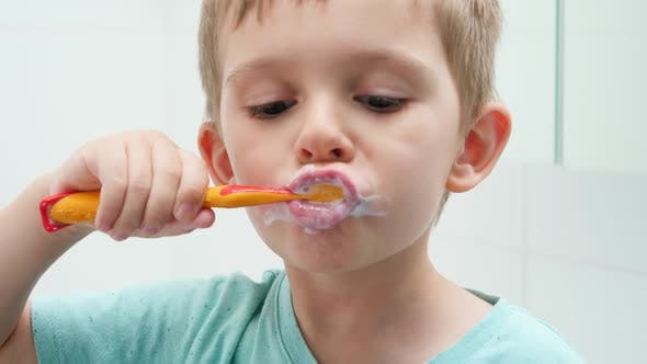 Portrait of Funny Toddler Boy Cleaning and Brushing Teeth at Morning