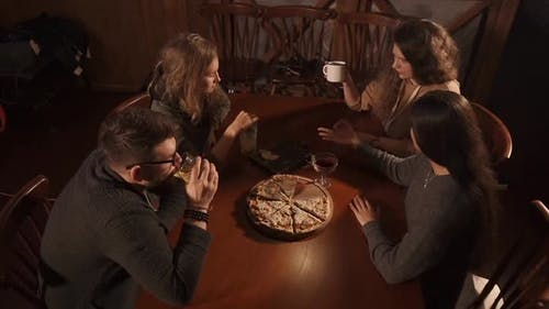 Relaxed Visitors of Pizzeria Are Chatting Sitting at Table Top View