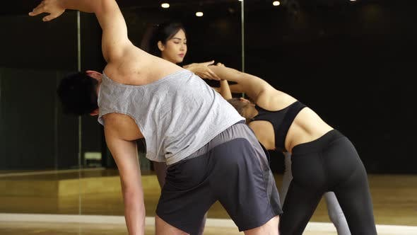 Asian Young Yoga Female Instructor Assisting a Male Beginner Balancing Flexibility Pose in Classroom