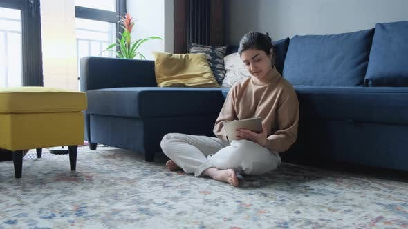 Mature Indian woman sitting Near sofa and websurfing on digital tablet