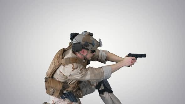 Soldier Is Shooting From Pistol Sitting on His Knee on Gradient Background.