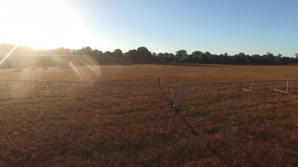 Aerial shot of irrigation equipment in field at sunrise
