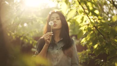 Asian Woman Blow on Dandelion at the Sunset