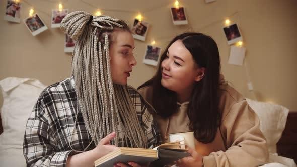 Thumbnail for Zwei Freundinnen liegen im Bett, lesen gemeinsam Buch und reden miteinander