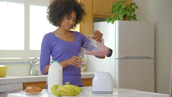 Thumbnail for Woman making fruit smoothie in kitchen