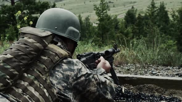Thumbnail for Soldier with a belt-fed machine gun. He pulls back on a lever on the firearm and pushes it back.