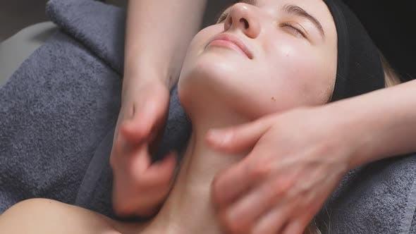 Attraktive Frau in einem Schönheitssalon liegt auf dem Bett und erhält eine Massage am Hals und Dekolleté