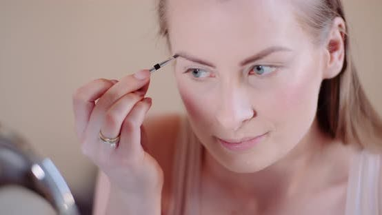 Cover Image for Woman Doing Makeup Painting Eyelashes with Mascara
