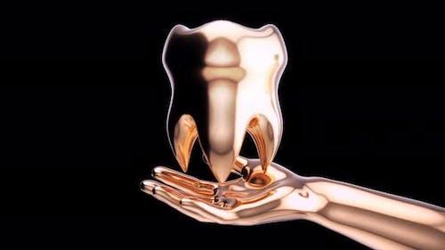 Goldene offene Hand mit einem goldenen Zahn