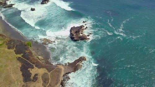 Aerial Top Down View of Ocean Waves Breaking on the Rocky Coast Line in Summer.