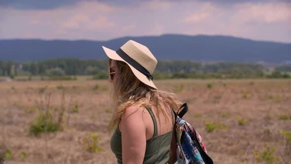 Thumbnail for Beautiful Woman in Hat and Sunglasses Walking on Summer Field Background. Traveling Woman with