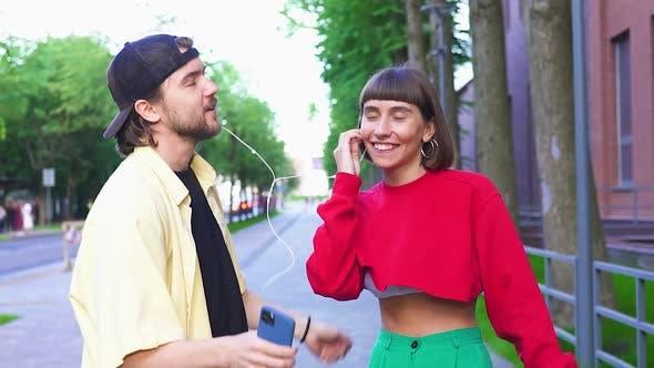 Cute Millenial Couple Dancing on Street Using Phone and Headphones
