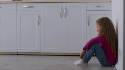 Lonely Little Abandoned Girl Sitting on Kitchen Floor Hiding From Her Arguing Parents Feeling