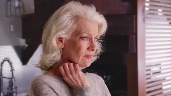 Close up of depressed older woman with pensive expression sighing indoors