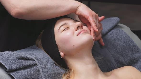 Junge Frau in einem schicken Schönheitssalon bekommt eine Gesichtsmassage und Schönheitsbehandlungen für die Hautpflege