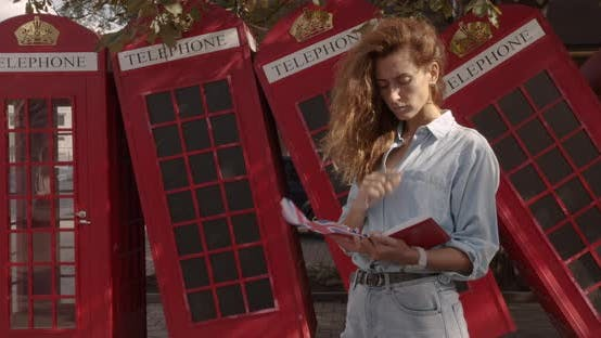 Thumbnail for Attractive Girl Walking on a Background of Red British Phones. Travel, Tourist Places Concept