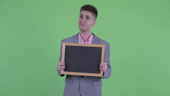 Thumbnail for Happy Young Businessman Thinking While Holding Blackboard