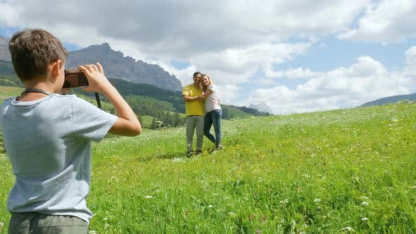 Boy (8 to 9) photographing parents in Alpine meadow, Alta Badia, Italy